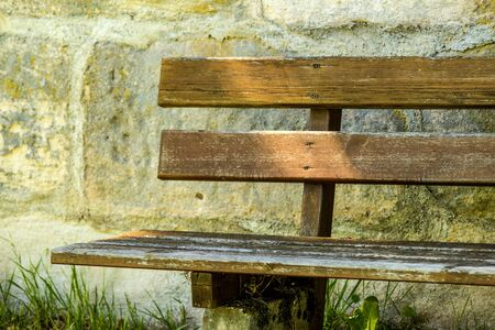 park bench at an old antique abbey wall