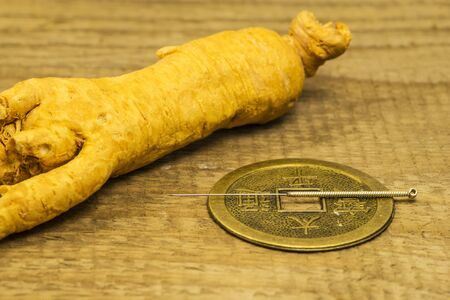Acupuncture needle on Chinese coin with ginseng root