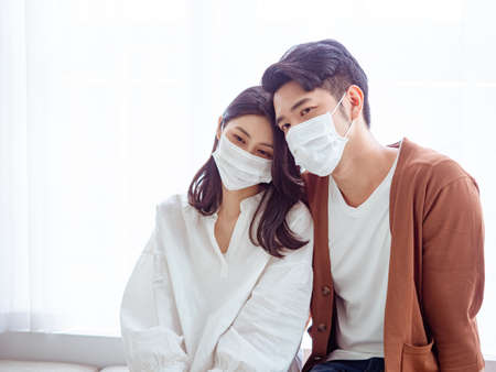 Young asian couple wearing surgical mask over white background