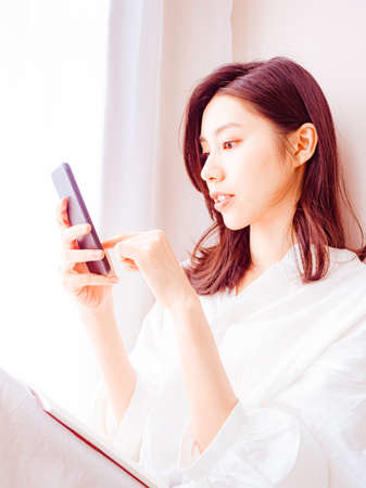 Young asian woman using smartphone at home 免版税图像