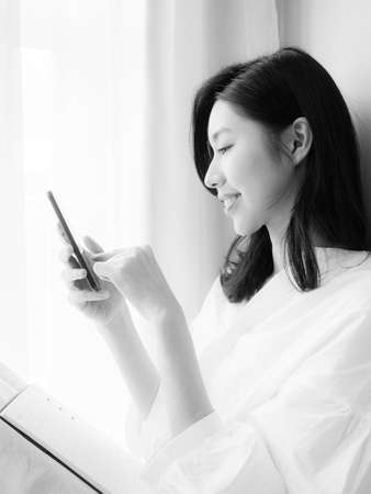 Young asian woman using smartphone at home in black and white