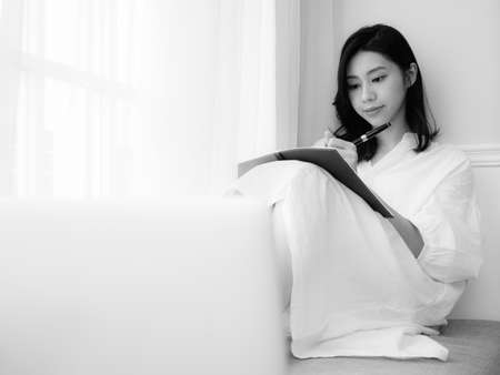 A beautiful Asian women writes something in a book in black and white