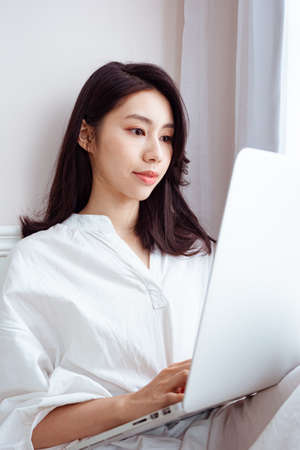 Young asian woman using computer at home
