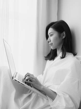 Young asian woman using computer at home in black and white
