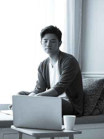 Asian young man sitting at the table in front of laptop computer