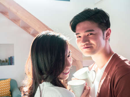 Young asian man and woman at home with cup of coffee in hands.