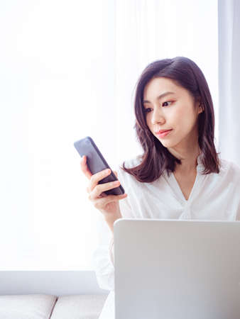 Young asian woman using smartphone at home Stock Photo