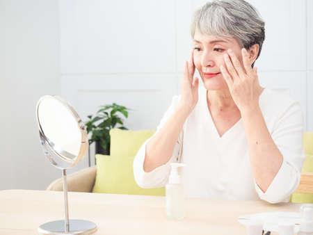 Senior asian woman who skin care at home. Banco de Imagens