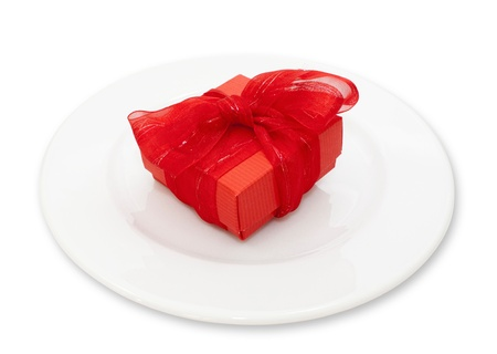 Red gift for a christmast evening on white plate photo