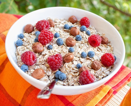 Oat nuts with fresh blueberries and raspberries and hazelnuts photo