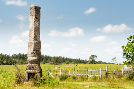 Chimney sitting in pasture with blue sky and trees in background Stock Photo