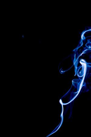Bluish-white smoke rising against black background