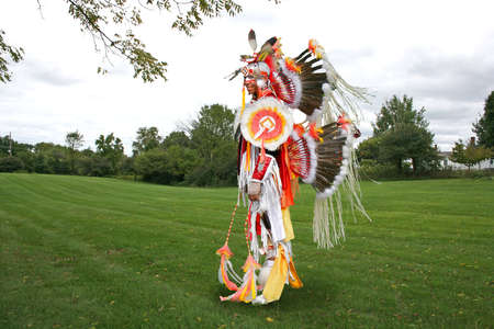 A young Native American  in war dance costume