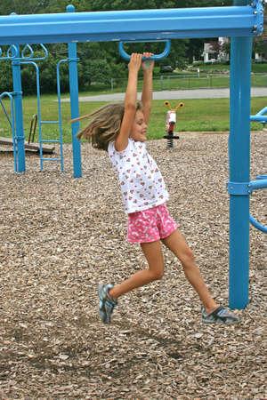 een klein meisje schuifdeuren op een bar in een park Stockfoto