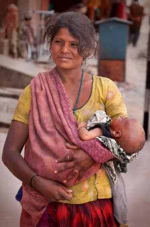 wees: een jonge moeder met haar baby bedelen in India