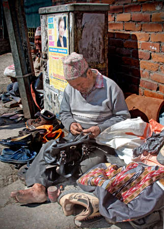A Nepalese shoe repairman on a strret of Kathmandu Editorial