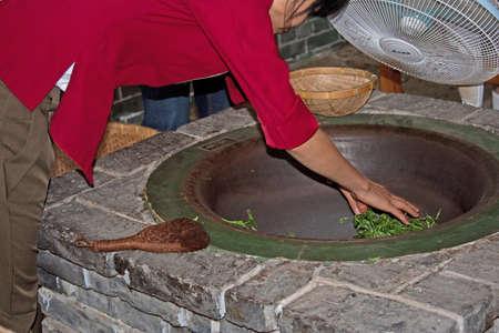 pekoe: pan-frying fresh tea leaves, Guilin, China Stock Photo