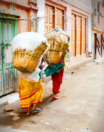laborious: 2 Nepalese women carrying loaded baskets on their backs.