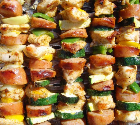 tasty barbecues with meat and vegetables on grill photo