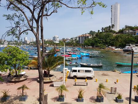 View of the fisherman's walk, with a van and several boats on Manzanillo beach, Acapulco