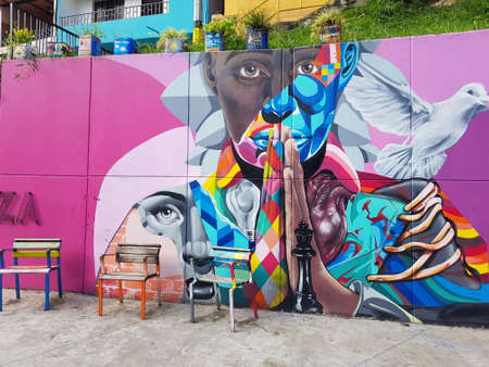 Medellin, Colombia-June 8 2019: Women's graffiti on a colorful pink background and some benches, in commune 13 Publikacyjne