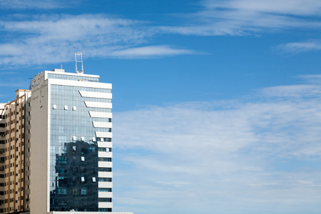 glass partition: Front of a modern glass building with sky and clouds Stock Photo