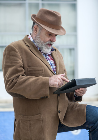 50 years old: Attractive man 50 years old with beard and hat with a tablet