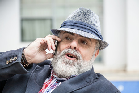 enticement: Attractive man 50 years old with beard and hat talking on phone