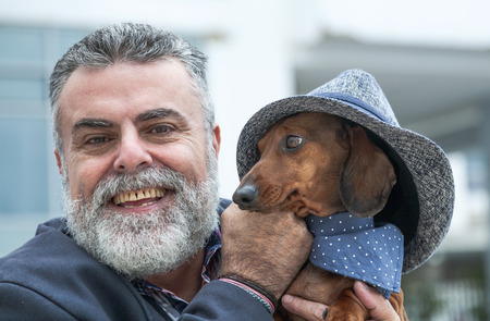 50 years old: Attractive man 50 years old with beard and hat with dog daschdund