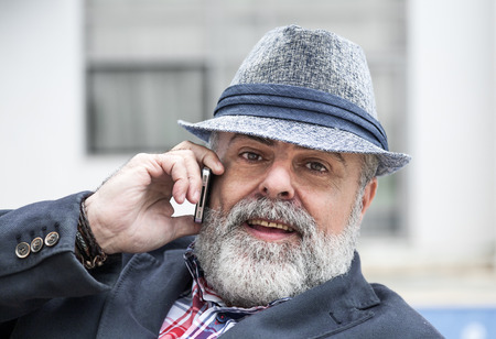 conceited: Attractive man 50 years old with beard and hat talking on phone
