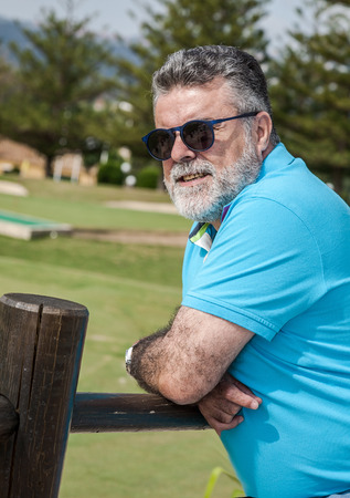 conceited: Attractive bearded man on a golf course in sunny day