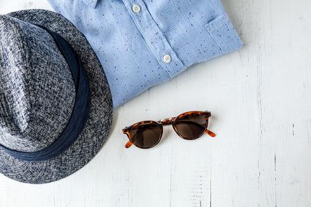 gafas de sol: Conjunto de ropa y diversos accesorios para hombres en mesa de madera vieja