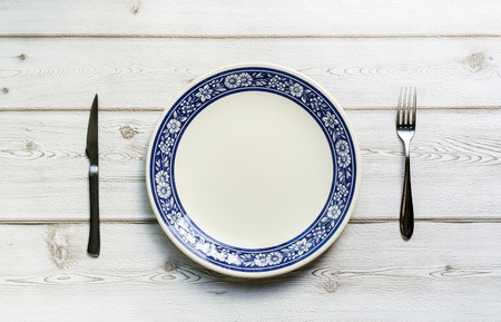 plato: knife and fork and plate on old wooden background