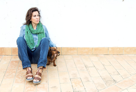 middleaged: Attractive woman playing with dachshund dog