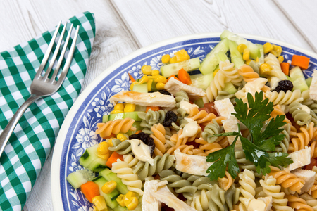 Pasta salad with chicken and corn tomato cucumber on wooden board