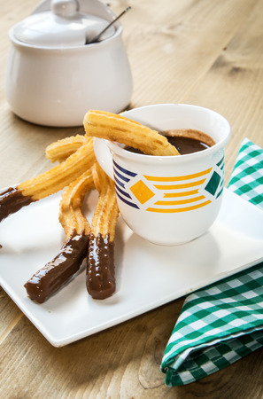 churros: Churros with hot chocolate and sugar on old wooden table Stock Photo