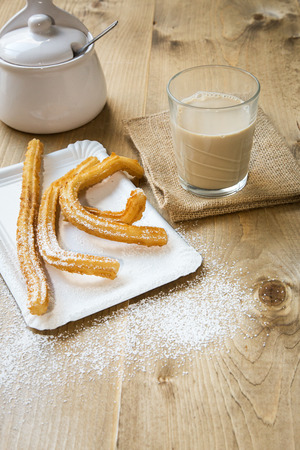 churros: Churros with coffee with milk and sugar on old wooden table