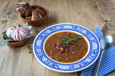 Traditional Spanish stew of white beans on old wooden table