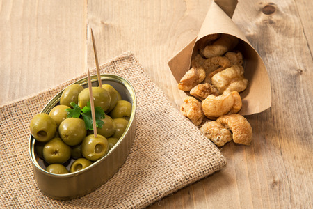 rinds: cap pork rinds and olives on old wooden table