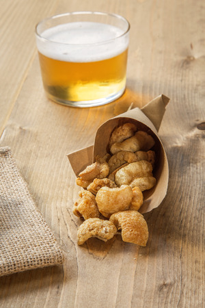 rinds: Beer cap pork rinds and olives on old wooden table