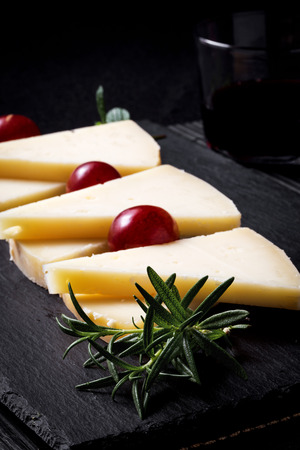 int: Typical Spanish Manchego cheese with grapes,m int and rosemary Stock Photo