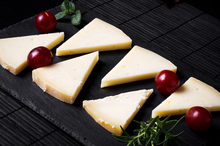 typical: Typical Spanish Manchego cheese with grapes,m int and rosemary Stock Photo