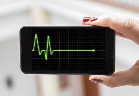 electrocardiograma: concepto móvil electrocardiograma: Mujer análisis de electrocardiograma en un teléfono móvil Foto de archivo