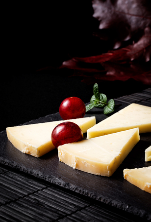 Typical Spanish Manchego cheese with grapes,mint and rosemary