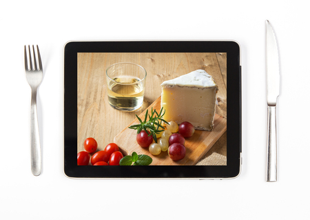 Photo typical Spanish Manchego cheese with grapes on tablet indoors