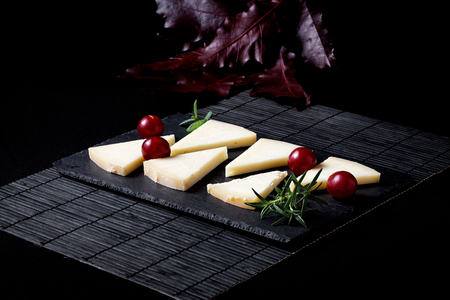 intense flavor: Typical Spanish cheese with wine, grapes and cherry tomatoes on old wooden table