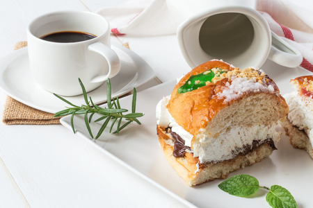 Kings cake with cream, coffee and mint, traditional spanish sweet on white wooden table