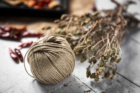 Roll thin rope with thyme and chilli peppers on old wooden table