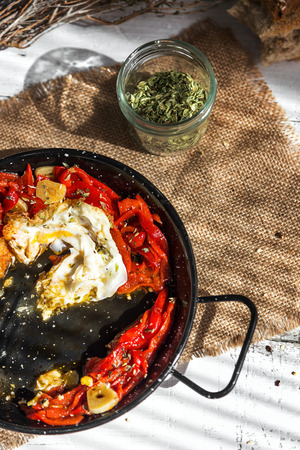 huevos estrellados: Fried eggs with peppers and rustic bread on white napkin striped and old wooden table