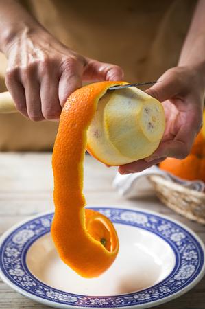 unrecognizable person: Unrecognizable person peeling orange skin off Stock Photo